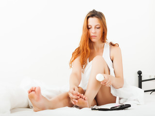 woman caring for feet with cosmetic cream