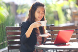 young businesswoman using laptop and drinking coffee outdoors. poster