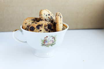 Biscuit cookies with chocolate chips in a vintage tea cup