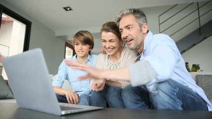 Happy family of three waving at camera during video call