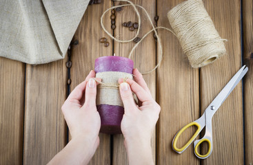 Top view of female hands make candle decorated with sackcloth