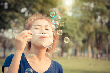 young woman play blowing bubble outdoor lifestyle vintage color