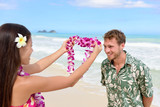 Fototapety Hawaii woman giving lei garland welcoming tourist
