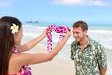 Fototapety Hawaii woman giving lei garland welcoming tourist