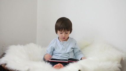 Cute little boy, reading a book at home
