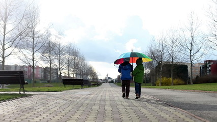 Two boys with umbrella, walking in the park on a sunny rainy day