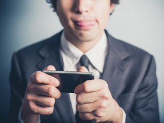 Businessman playing games on his smartphone