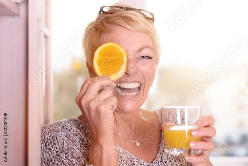 Lachende Frau hält eine Orangenscheibe an ihr Auge
