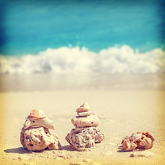 Retro image of coral pyramids on beach.