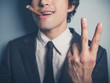 Young businessman with cigar showing rude gesture - 80894763