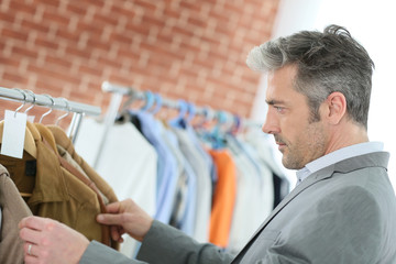 Mature man choosing clothes in shop