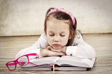 Little girl sleeping on the books