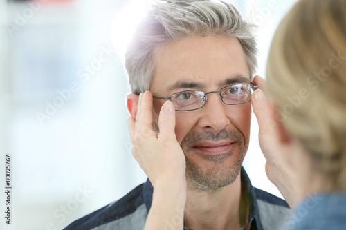 Fototapeta Mature man in optical store trying eyeglasses on
