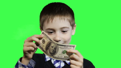 Cheerful little boy close-up, holding dollars on a green