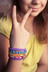 Caucasian girl showing two fingers with rubber loom bracelets
