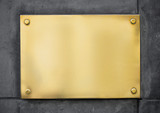 blank gold metal signboard or nameboard on concrete wall