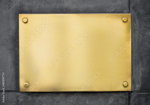Leinwandbild Motiv blank gold metal signboard or nameboard on concrete wall