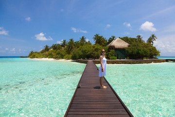 Girl in white dress standing on footbridge in the Maldives