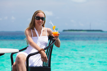 Girl in white dress drinking juice on a beach