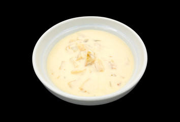 Bowl of clam chowder on a black background