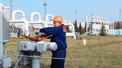 worker closes recirculation valve on gas compressor station