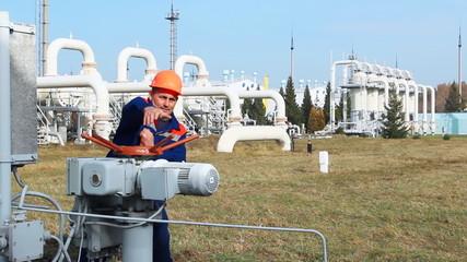 worker opens recirculation valve on gas compressor station