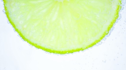 Sparkling water with bubbles and lime slice on white