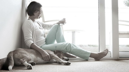Sad woman siting on the floor near the friendly dog