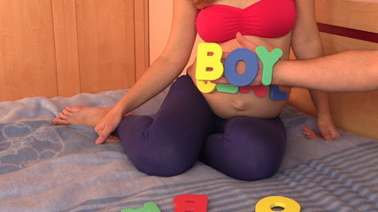 Pregnant woman belly with word girl and man hand with boy word