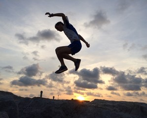 Male runner leaping at sunrise