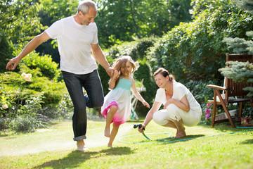 Vater und Mädchen springen über Spritzwasser aus Gartenschlauch