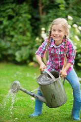 Mädchen mit Zinkgießkanne im Garten auf grüner Wiese