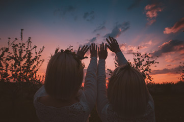 Twin girls stretching hands to the sky