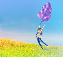 Happy girl flying with balloons