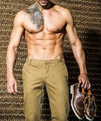 Handsome muscular man posing against goldt elegant background