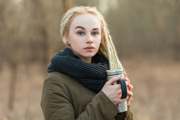 Young blonde woman with thermos cup cold season outdoors