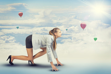 Woman standing in running start pose. Sky with clouds and air