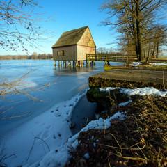 Winterlandschaft mit Bootshaus und See