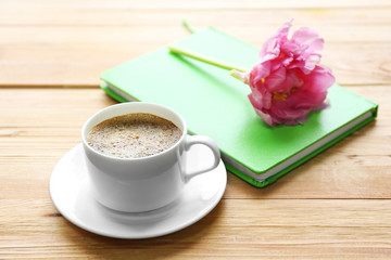 Cup of coffee with notebook and fresh flower