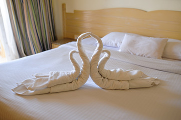 Tucked bed with swans out of towels in a hotel room