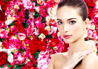 Beautiful woman on a floral background with red and white roses
