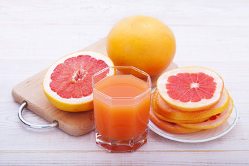 glass of juice with fresh citrus on white wooden table.