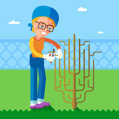 Garden. The woman cuts off branches using pruning shears.