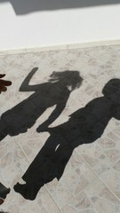 Ombra di bambine che saltano tenendosi per mano