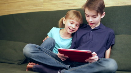 Siblings using a tablet computer panning
