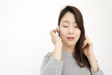 Beautiful asian woman with headphones listening music