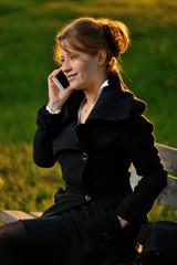 Ragazza  sorridente seduta sulla panchina con  lo smartphone