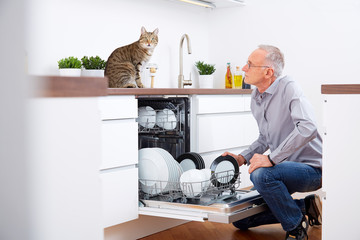 Senior man with cat in the kitchen, empty out the dishwasher