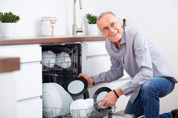 Senior man in kitchen, empty out the dishwasher 6