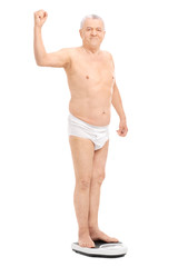 Semi-dressed senior flexing his bicep on a weight scale